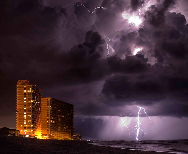 Lighting from an approaching thunder storm strikes near the shore in Panama City Beach, Fla., on Thursday, July 10, 2014. (Photo by Brennen Smith/AP Photo/The Decatur Daily)