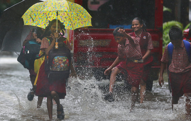 A schoolgirl reacts to rainwater being splashed on her, in a flooded street in Mumbai, India, Tuesday, June 28, 2016. (Photo by Rafiq Maqbool/AP Photo)