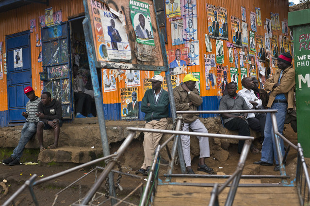 Kenyans sit under election posters in the Kibera slum in Nairobi, Kenya, Monday August 7, 2017. (Photo by Jerome Delay/AP Photo)