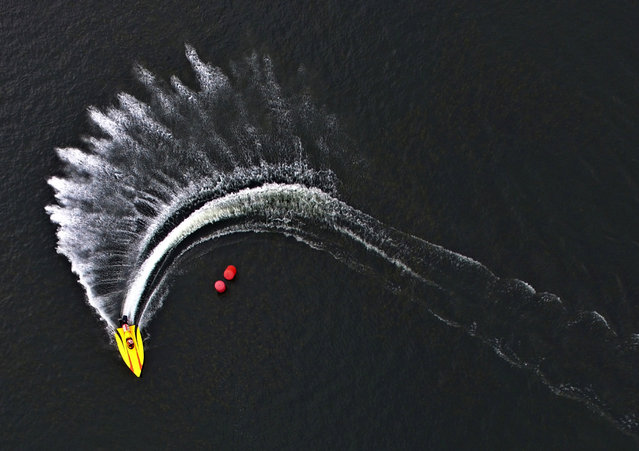 An aerial view shows a speed boat competing during the Russian powerboat championship on the Yenisei River in Krasnoyarsk, Siberia, Russia, July 1, 2017. (Photo by Ilya Naymushin/Reuters)