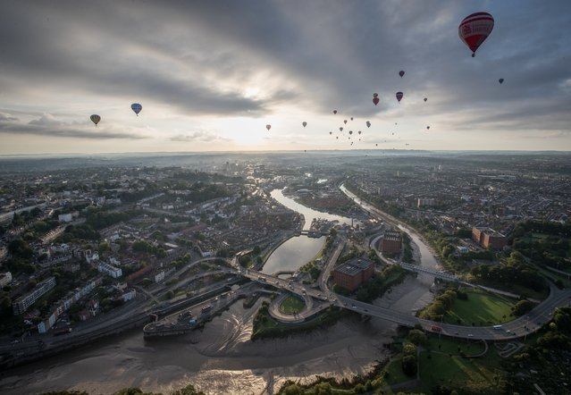 Hot air balloons take to the skies as they participate in the mass assent at sunrise on the second day of the Bristol International Balloon Fiesta on August 11, 2017 in Bristol, England. More than 130 balloons have gathered for the four day event, now in its 39th year and now one of Europe's largest annual hot air balloon events, being hosted in the city that is seen by many as the home of modern ballooning. (Photo by Matt Cardy/Getty Images)