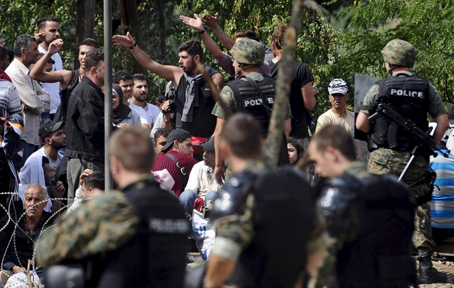 Macedonian special policemen guard the border as more than a thousand immigrants wait at the border line of Macedonia and Greece to enter Macedonia near the Gevgelija railway station August 21, 2015. (Photo by Ognen Teofilovski/Reuters)