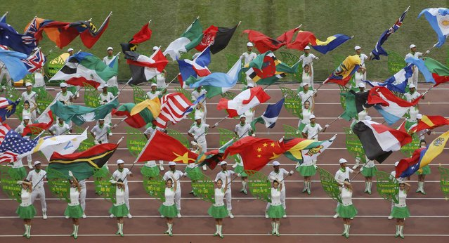 Performers hold up flags of particpating nations during the opening ceremony of the 15th IAAF World Championships at the National Stadium in Beijing, China August 22, 2015. (Photo by Fabrizio Bensch/Reuters)