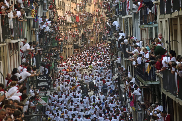 Revelers go on the way of the Estafeta street beside Fuente Ymbro fighting bulls as people look on from balconies during the first running of the bulls at the San Fermin Festival, in Pamplona, norther Spain, Thursday, July 7, 2016. Revelers from around the world arrive to Pamplona every year to take part in some of the eight days of the running of the bulls. (Photo by Alvaro Barrientos/AP Photo)