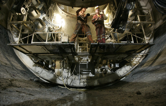 Workers operate on a tunnel drilling machine inside the Gotthard base tunnel in Erstfeld, central Switzerland May 15, 2008. (Photo by Michael Buholzer/Reuters)