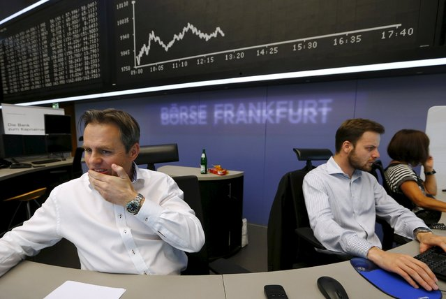 A trader reacts at his desk in front of the DAX board at the Frankfurt stock exchange, Germany, August 24, 2015. (Photo by Ralph Orlowski/Reuters)