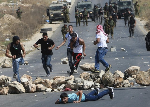 Palestinian protesters run for cover as Israeli soldiers fire rubber bullets during clashes following a demonstration against Israeli military action in Gaza, at the Beit Fourik checkpoint near the West Bank city of Nablus August 15, 2014. (Photo by Abed Omar Qusini/Reuters)