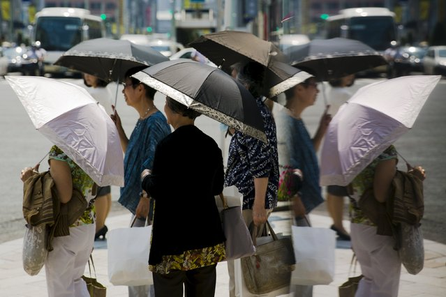 Women hold parasols as they wait at a pedestrian crossing on a hot day in Tokyo, July 27, 2015. (Photo by Thomas Peter/Reuters)