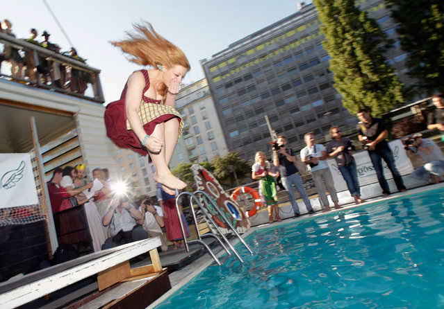 "A participant of the the ""Dirndlspringen"" contest jumps into a swimming pool in Vienna, on June 16, 2012. At Dirndlspringen, a jury votes on the best performance of people jumping into a swimming pool in traditional Austrian Dirndl dresses. (Photo by Herwig Prammer/Reuters)"