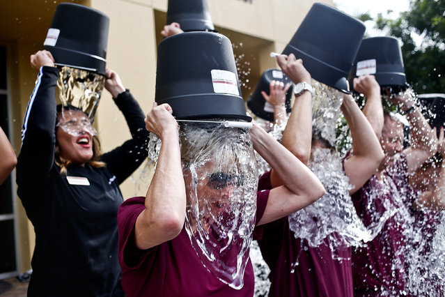 Debbie Wallace, center, dumps a bucket of ice water on her head along with her coworkers as they participate in an Ice Bucket Challenge at the Woodruff Institute in Naples, FL on Tuesday, August 19, 2014. Wallace, a physician assistant at Woodruff, lost her brother Chester to ALS two weeks before and challenged her coworkers in the challenge. (Photo by Scott McIntyre/AP Photo/Naples Daily News)