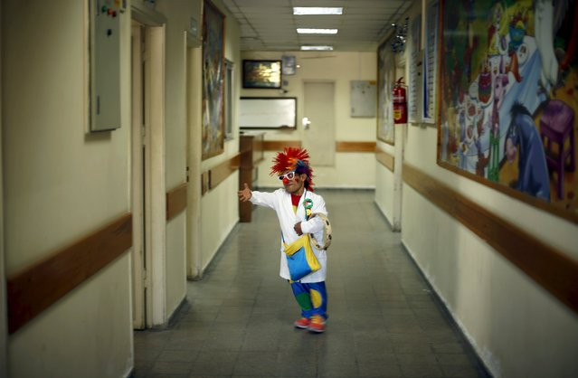 A Palestinian social activist working for the International South South Cooperation (Cooperazione Internazionale Sud Sud, or CISS) entertain children who are cancer patients, while dressed as a clown, inside a hospital in Gaza City August 31, 2015. (Photo by Mohammed Salem/Reuters)