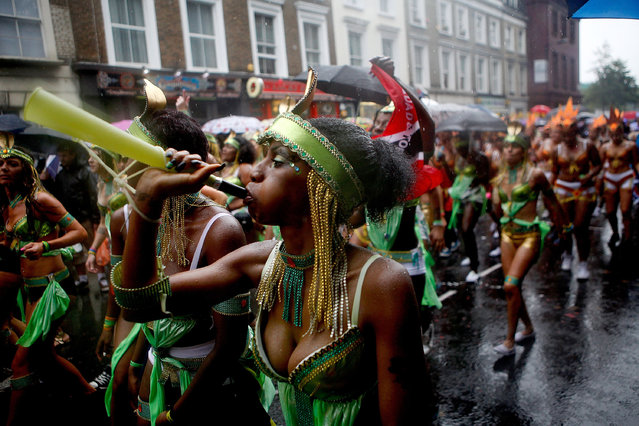 Revellers dance through the rain soaked streets of West London during the Notting Hill Carnival on August 25th, 2014 in London, England. Despite the bad weather over 1 million visitors are expected to attend the two-day event which is the largest of its kind in Europe. The event has taken place on the West London streets every August Bank Holiday weekend since 1964. (Photo by Mary Turner/Getty Images)