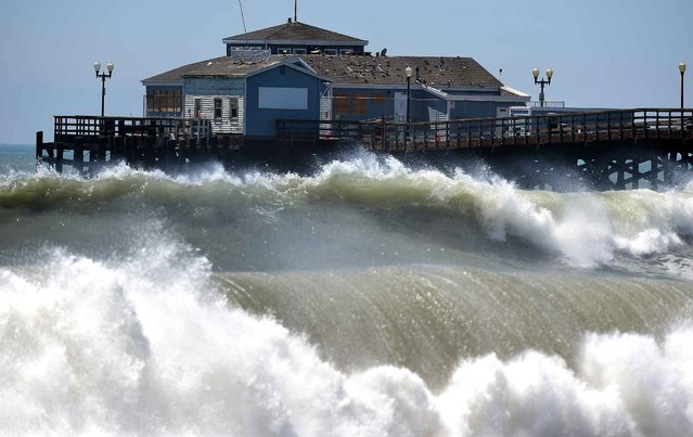 Big waves crash ashore and into the pier at Seal Beach, California on August 27, 2014, where some overnight flooding occurred as the surging ocean water resulting from Hurricane Marie almost reached beachfront homes. And as surfers prep for what could be some of the biggest swells of the year, county and city officials are using tractors to fill in sand berms along coastal beaches, in a hopeful effort to avoid any flooding or other damage resulting from Hurricane Marie. (Photo by Frederic J. Brown/AFP Photo)
