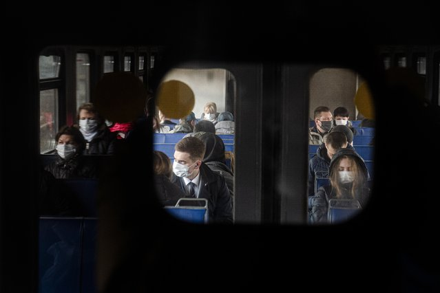 People wearing face masks to protect against coronavirus, ride a suburban train near Moscow, Russia, Thursday, April 16, 2020. Russian President Vladimir Putin has ordered most Russians to stay off work until the end of April as part of a partial economic shutdown to stymie the spread of the coronavirus. (Photo by Victor Berezkin/AP Photo)