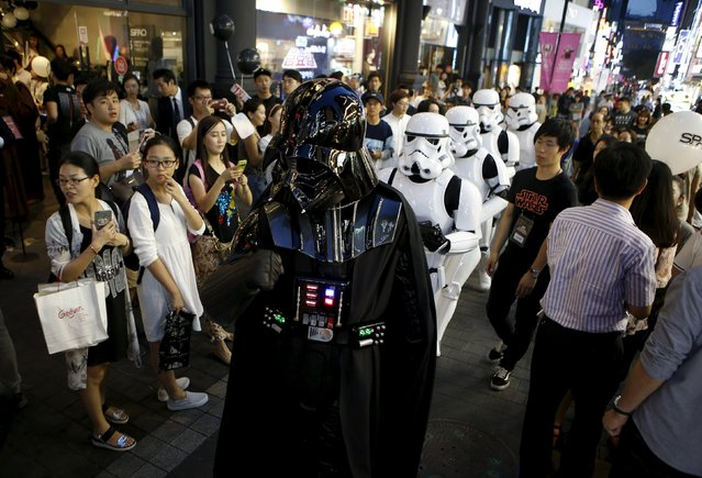 """Workers dressed as Darth Vader (front) and Storm Troopers from """"Star Wars"""" march on a street as tourists watch at Myeongdong shopping district in Seoul, South Korea, September 4, 2015. (Photo by Kim Hong-Ji/Reuters)"""