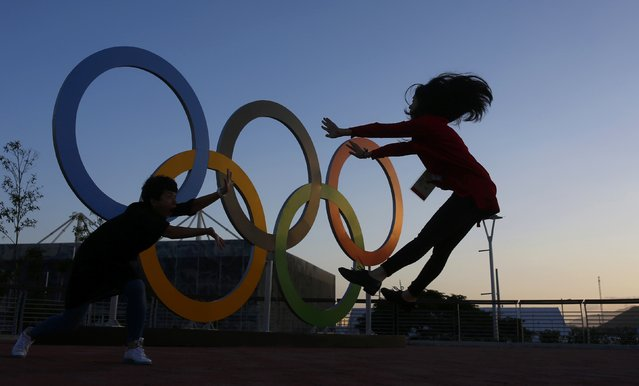 Chinese journalists jump in front of the rings at sunset in the Olympic Park in Rio de Janeiro, Brazil on July 31, 2016. (Photo by Nacho Doce/Reuters)