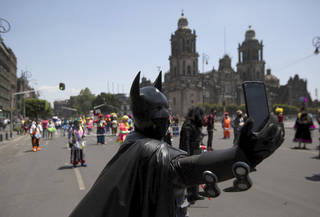 A street performer dressed as Batman takes a selfie during a protest in Mexico City, Thursday, April 30, 2020. The city's street performers marched to Mexico City's main square the Zocalo, protesting in front of the national palace against restrictions designed to help stop the spread of COVID-19 disease, barring them from working on the streets. (Photo by Fernando Llano/AP Photo)