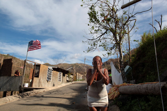 Ruth Santiago refreshes herself with water from a pipe after Hurricane Maria destroyed the town's bridge in San Lorenzo, Morovis, Puerto Rico, October 4, 2017. (Photo by Alvin Baez/Reuters)