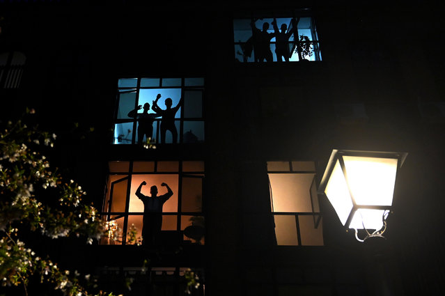 Neighbours in a residential building gesture and applaud from their windows to pay tribute to the healthcare workers dealing with the COVID-19 disease in Madrid, on March 28, 2020, during a national lock-down to prevent the spread of the novel coronavirus pandemic. The death toll from coronavirus in Spain surged over 5,600 today after a record 832 people died in 24 hours, and the number of infections soared over 72,000, the government said. Spain has the world's second-highest coronavirus death toll after Italy with 5,690 fatalities. The number of confirmed cases have jumped to 72,248 as the country moves to significantly increase testing. (Photo by Gabriel Bouys/AFP Photo)
