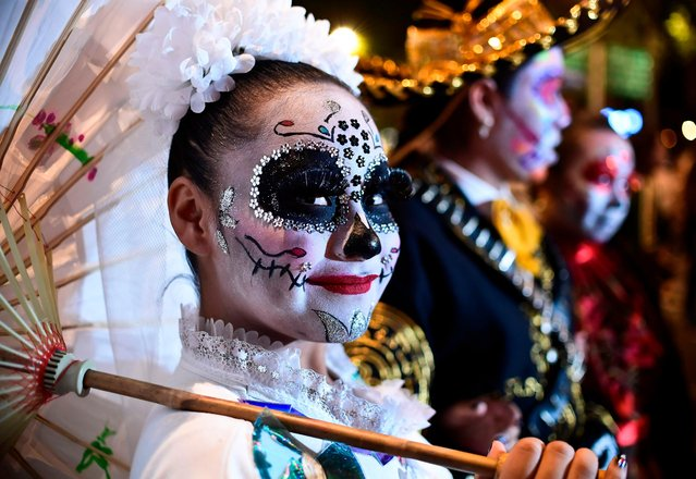 "People fancy dressed as ""Catrina"" take part in the ""Catrinas Parade"" along Reforma Avenue, in Mexico City on October 22, 2017. (Photo by Ronaldo Schemidt/AFP Photo)"