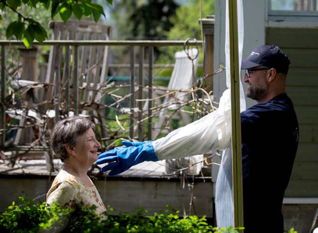 "Alex Montagano demonstrates his ""Hugging Station"" with neighbour Sharon Pearce-Anderson, that he built to embrace family members amid the coronavirus disease (COVID-19) precautions in Montreal, Quebec, Canada on May 21, 2020. (Photo by Christinne Muschi/Reuters)"