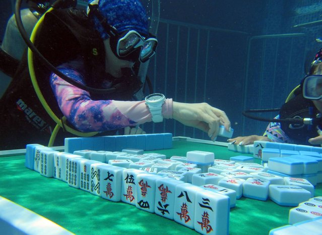 This photo taken on August 7, 2016 shows mahjong enthusiasts playing mahjong under water in a swimming pool at a diving club in the Chinese city of Chongqing. Only participants with proper diving certification were allowed to take part in the underwater competition. (Photo by AFP Photo/Stringer)