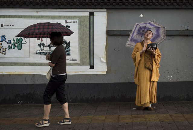 A Chinese Buddhist monk holds a begging bowl as he waits for alms from passerby while standing in the rain on September 2, 2014 in Beijing, China. (Photo by Kevin Frayer/Getty Images)
