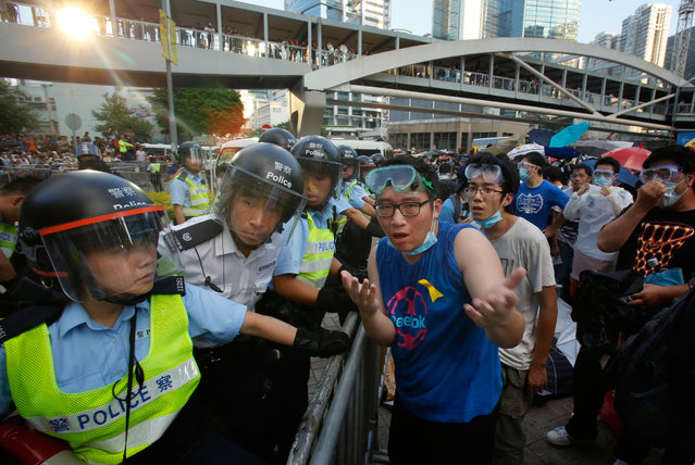 A student protester tries to negotiate with riot police as they fire pepper spray in to the crowd as thousands of protesters surround the government headquarters in Hong Kong Sunday, September 28, 2014. Hong Kong police used tear gas on Sunday and warned of further measures as they tried to clear thousands of pro-democracy protesters gathered outside government headquarters in a challenge to Beijing over its decision to restrict democratic reforms for the city. (Photo by Wally Santana/AP Photo)