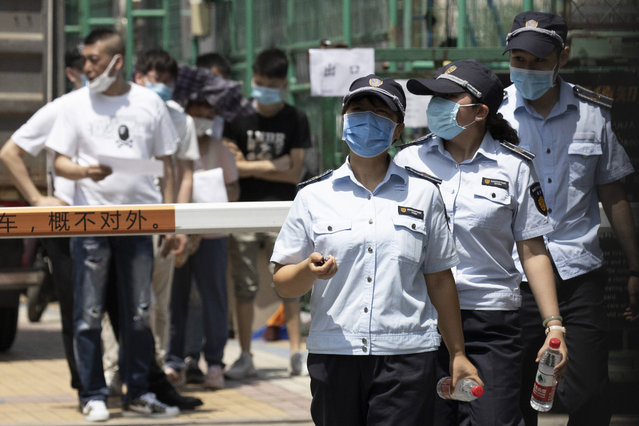 Workers leave from a coronavirus testing center set up outside a sports facility in Beijing, Tuesday, June 16, 2020. China reported several dozen more coronavirus infections Tuesday as it increased testing and lockdown measures in parts of the capital to control what appeared to be its largest outbreak in more than two months. (Photo by Ng Han Guan/AP Photo)