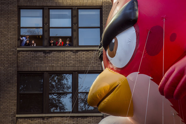 People watch as the balloon Red from Angry Birds moves through Sixth Avenue during the Macy's Thanksgiving Day Parade in New York, Thursday, November 23, 2017. (Photo by Andres Kudacki/AP Photo)