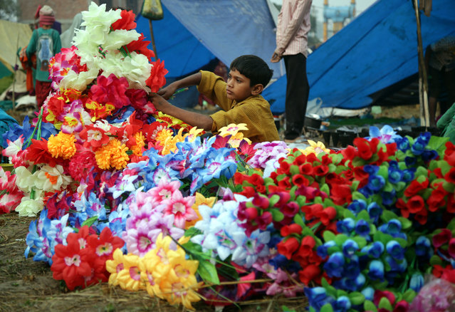 An Indian boy prepares the bunches of artificial flowers for sale during the annual Farmers Fair at Shama Chak Jhiri, some 22 km from Jammu, the winter capital of Kashmir, India, 03 November 2017. Every year hundreds of vendors from Punjab, Haryana, Rajasthan and Utter Pradesh come to farmers fair to setup their business in a week-long fair. Farmers in huge numbers from all over India gather to pay tribute to the Samadhi or tomb of legendary farmer Baba Jit Mal, popularly known as Baba Jitto who sacrificed his life for the liberation of the farming community. (Photo by Jaipal Singh/EPA/EFE)