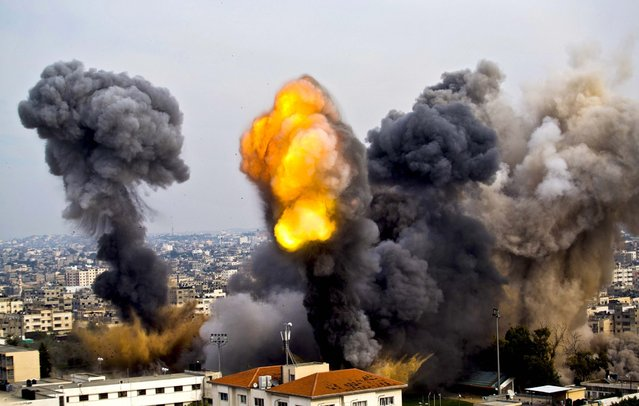 Smoke billows from the site of an Israeli air strike in Gaza City, November 21, 2012. Israeli aircraft pounded Gaza with at least 30 strikes overnight, hitting government ministries, smuggling tunnels, a banker's empty villa and a Hamas-linked media office. (Photo by Bernat Armangue/Associated Press)
