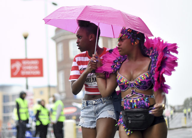 Two women shelter from the rain during the first day of the Notting Hill Carnival on August 28, 2016 in London, England. (Photo by Ben A. Pruchnie/Getty Images)