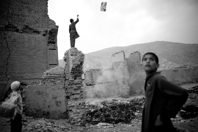 An Afghan youth flies a kite on the remains of a building during the Muslim holy month of Ramadan on August 16, 2010 in Kabul, Afghanistan. Muslims all over the world are supposed to go without food, drink, smoking and s*x from sunrise to sunset during the month of Ramadan in order to purify themselves and concentrate their mind on Islamic teachings. (Photo by Majid Saeedi/Getty Images)