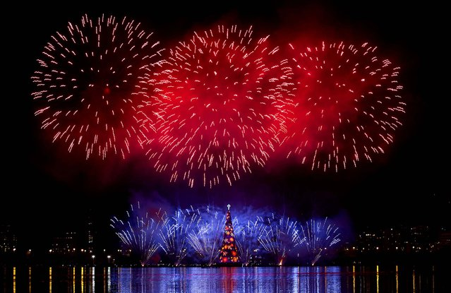 Fireworks explode over the floating Christmas tree in Lagoa Lake at the annual holiday tree lighting event in Rio de Janeiro, Brazil. The Christmas tree, decorated with millions of lights, is believed to be one of the largest in the world. (Photo by Silvia Izquierdo/Associated Press)