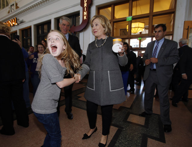 Ten-year-old Macy Friday, front left, reacts as she looks back at her family after meeting Hillary Clinton, front right, as she campaigns for U.S. Sen. Mark Udall, D-Colo., back, during a stop in the newly-renovated Union Station in Denver on Monday, October 13, 2014. Clinton appeared at an event to raise money for Udall's current re-election campaign and then headed to Las Vegas for another appearance on Monday night. (Photo by David Zalubowski/AP Photo)