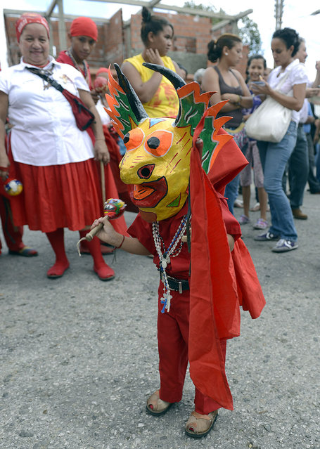 A young member of the Dancing Devils performs during a demonstration in the Venezuelan village of Yare, Miranda State, on December 7, 2012. On December 6, the UNESCO declared the Dancing Devils as an Intangible Cultural Heritage of Humanity. Every Corpus Christi day, the Dancing Devils, in colourful costumes and wearing grotesque masks, perform their ritual during the Dancing Devils of Yare folkloric festivity. (Photo by Juan Barreto/AFP Photo)