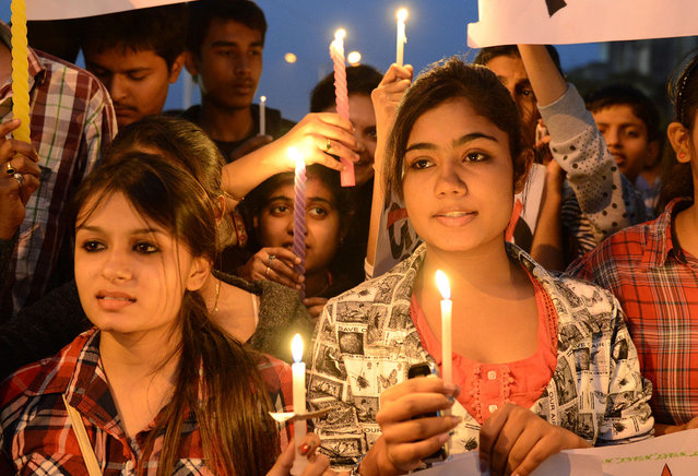Indian youth hold candles and placards as they take part in a candlelight vigil following the gang rape of a student last week in the Indian capital during a rally in Ahmedabad, on December 23, 2012. (Photo by Sam Panthaky/AFP Photo)