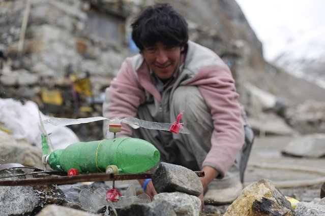 A young porter plays with a helicopter he made from plastic bottles, and which is powered by a water-jet of melting glacial water, at Khoburtse along the K2 base camp trek in the Karakoram mountain range in Pakistan September 9, 2014. (Photo by Wolfgang Rattay/Reuters)