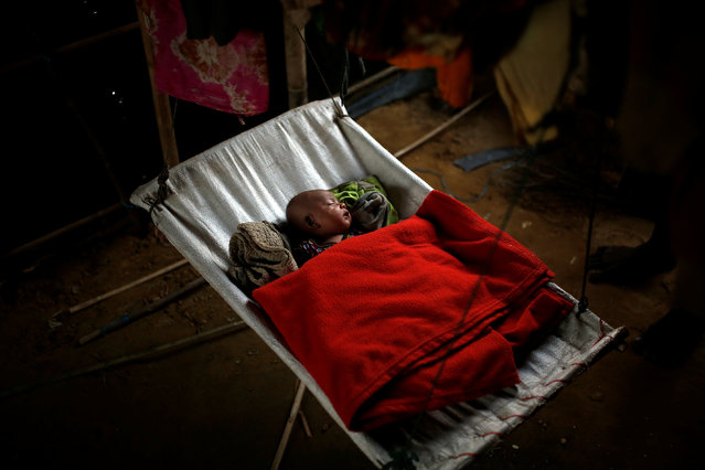 A Rohingya refugee baby girl sleeps inside her family's temporary shelter at the Balukhali refugee camp near Cox's Bazar, Bangladesh December 20, 2017. (Photo by Alkis Konstantinidis/Reuters)