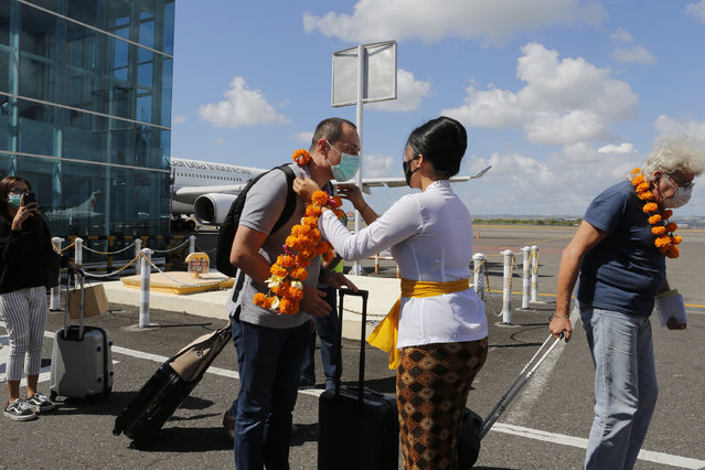An airport officer, center right, welcomes a passenger on his arrival at Bali airport, Indonesia on Friday, July 31, 2020. Indonesia's resort island of Bali reopened for domestic tourists after months of lockdown due to a new coronavirus. (Photo by Firdia Lisnawati/AP Photo)
