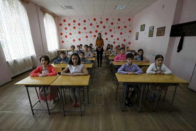 Teacher Ekaterine Tsipuria poses for a picture with year 5 schoolchildren at a public school in Tbilisi, Georgia, June 8, 2015. (Photo by David Mdzinarishvili/Reuters)