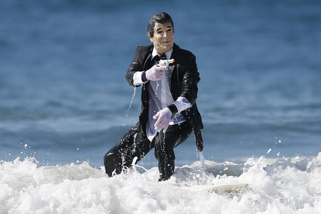 JohnPaul Trotter, 31, rides a wave dressed as President Ronald Reagan after competing in the 7th annual ZJ Boarding House Haunted Heats Halloween surf contest. (Photo by Lucy Nicholson/Reuters)
