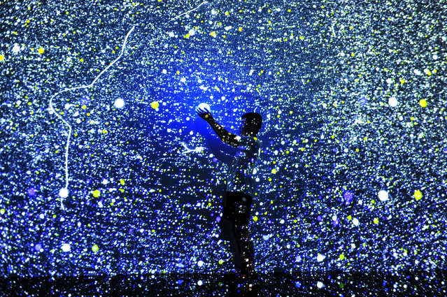"An experiencer holding a luminous body becomes a member of the stars for a ""deep space"" experience. Qingdao, Shandong province, China, August 2, 2020. (Photo by Costfoto/Barcroft Media via Getty Images)"