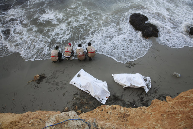 In this Saturday, October 3, 2015 photo, members of the Libyan Red Crescent wash their hands at the shore after they put bodies in the bags as they were found washed up in the eastern shore of Tripoli, Libya. A spokesman for the Red Crescent said the bodies of at least 95 migrants have been found washed ashore over the past five days. (Photo by Mohamed Ben Khalifa/AP Photo)