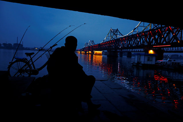 A man looks across Yalu River towards North Korea as he sits next to the bridge that connects China's Dandong, Liaoning province and North Korea's Sinuiju, September 10, 2016. (Photo by Thomas Peter/Reuters)