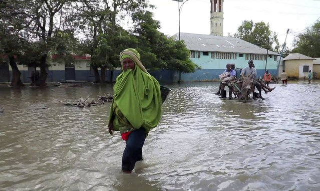 In this image made from video, residents move through floodwaters on foot and using a donkey cart in Afgoye, Somalia Sunday, August 9, 2020. Severe flooding continues to displace thousands of people in Somalia and the government in recent days has issued new warnings to communities living along the Jubba and Shabelle rivers. (Photo by AP Photo/Stringer)