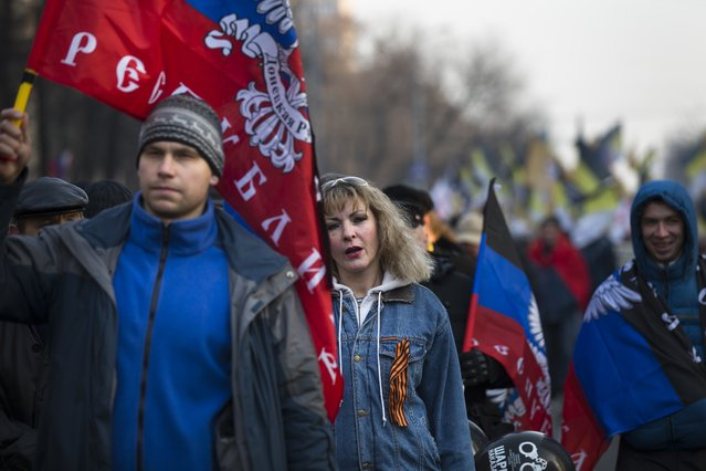 Russian nationalists carry flags of Donetsk People's Republic during a march in support of pro-Russian separatists fighting with Ukrainian government forces in eastern Ukraine in Moscow to mark People's Unity Day, a public holiday in Russia, on Tuesday, November 4, 2014. (Photo by Alexander Zemlianichenko/AP Photo)