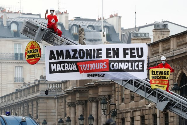 """Greenpeace activists stand on a fire truck during an action in front of the Elysee Palace to protest against the ongoing damage to the Amazon rain forest, in Paris, France, September 10, 2020. The slogan reads """"Amazon Rain Forest On Fire. Macron still complicit"""". (Photo by Christian Hartmann/Reuters)"""