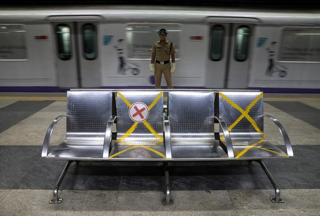 A security guard wearing a face shield stands next to chairs bearing social distancing signs at a metro train station ahead of its operation restart, amidst the coronavirus disease (COVID-19) spread, in Kolkata, India, September 9, 2020. (Photo by Rupak De Chowdhuri/Reuters)
